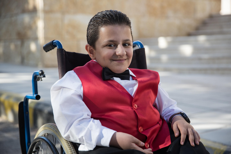 محمد يجلس خارجا في كرسيه المتحرك يبتسم